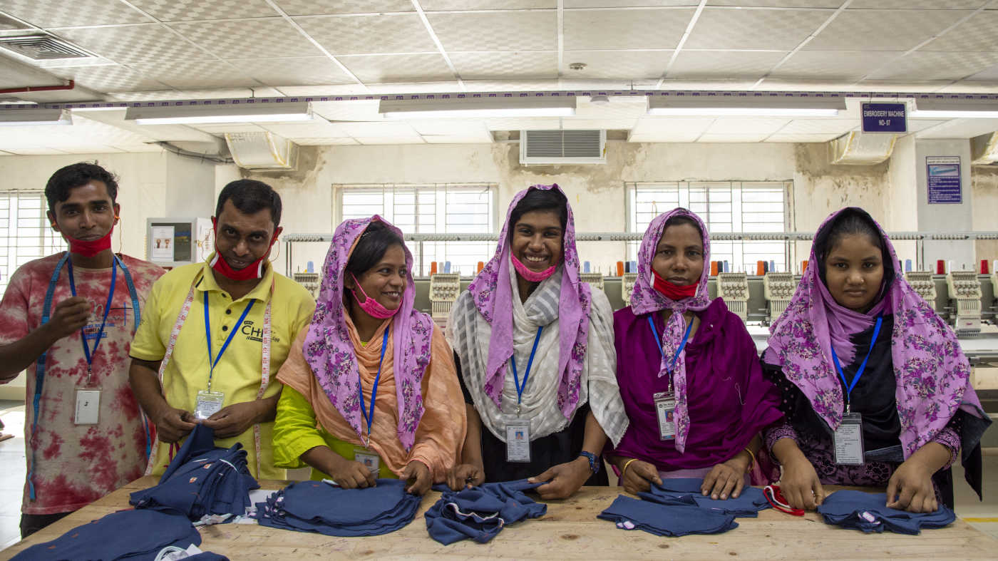 Factory workers facing the camera smiling and laughing together